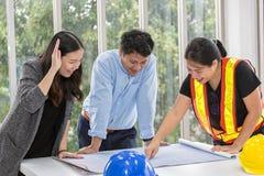 3 инженера работая конференц-зал на офисе 3 работника говорят план строительства Плотник электриков или стоковые изображения rf