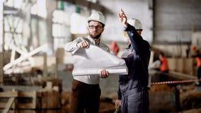 2 инженера стоя в строительной площадке и держа план строительства Люди в белых защитных шлемах работая обсуждающ detailes сток-видео