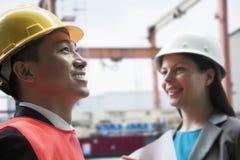 2 инженера усмехаясь в защитном workwear снаружи в грузя дворе Стоковые Изображения
