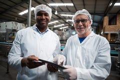 2 инженера фабрики с цифровой таблеткой усмехаясь в производственной установке пить Стоковые Изображения RF