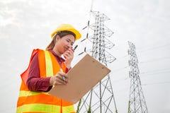 Инженерство женщины работая на высоковольтной башне Стоковая Фотография