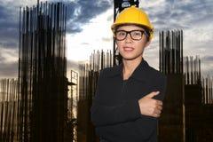 Инженерство женщин в усмехаться на конструкции в сумерк Стоковые Изображения RF