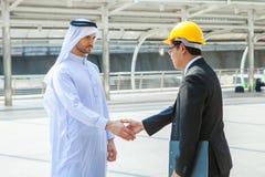 Инженерство рук арабского бизнесмена тряся азиатское над делом n Стоковое Изображение RF