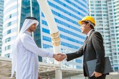 Инженерство рук арабского бизнесмена тряся азиатское над делом n Стоковое Изображение