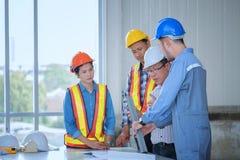 Инженеры встречающ, работающ и смотрящ дома светокопию внутри стоковое изображение