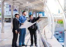 Инженеры встречая на террасе na górze строительной площадки Сотрудники обсуждая Босс и работник спорят Переговор в команде стоковое фото