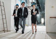 Инженеры в защитных шлемах имеют переговор стоковое фото rf