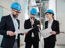 Инженеры в защитных шлемах имеют переговор стоковое фото
