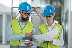 Инженеры в защитных шлемах имеют переговор стоковая фотография rf