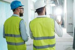 Инженеры в защитных шлемах имеют переговор стоковые изображения
