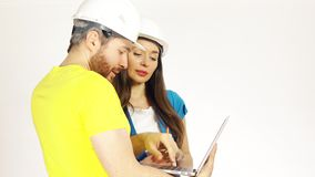 2 инженеры или архитектора нося имеемые шляпы для того чтобы обсудить проект и использовать ноутбук сток-видео