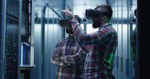 Инженеры ИТ используя стекла VR в комнате сервера видеоматериал