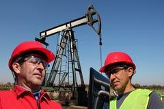 Инженеры нефти смотря портативный компьютер стоковое изображение