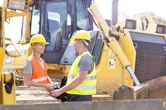 Инженеры обсуждая на строительной площадке стоковые изображения