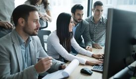 Инженеры по программномы обеспечению работая в офисе на проекте совместно стоковые изображения