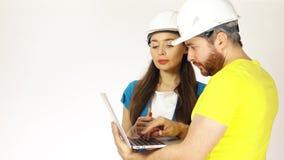 Инженеры по строительству и монтажу или архитекторы обсуждают проект и использовать ноутбук сток-видео