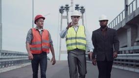 Инженеры по строительству и монтажу идя на пандус шоссе Стоковое фото RF
