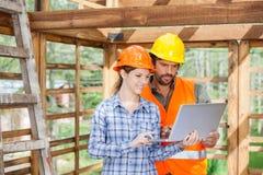 Инженеры работая на компьтер-книжке на строительной площадке Стоковая Фотография