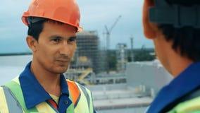 Инженеры среднего возраста мужские обсуждая проект на строительной площадке акции видеоматериалы
