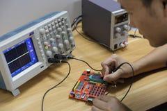 Инженер Œmale ¼ ï монтажной платы электронных устройств и электронный используя осциллограф в лаборатории стоковые изображения