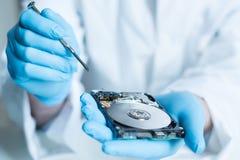 Инженер лаборатории работая на сломленном жёстком диске Стоковая Фотография RF