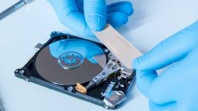 Инженер лаборатории работая на сломленном жёстком диске Стоковые Изображения