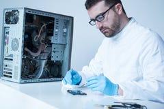 Инженер лаборатории работая на сломленном жёстком диске Стоковые Изображения RF