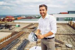 инженер архитектора работая и усмехаясь на конструкции с защитным шлемом в руке стоковое изображение