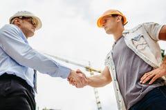 Инженер архитектора тряся руки другая рука на строительной площадке Сыгранность дела, сотрудничество, collaboratio успеха Стоковое Изображение