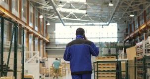 Инженер внутри в голубой форме идет через фабрику и говорит на мобильном телефоне задний взгляд акции видеоматериалы