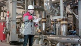 Инженер внутри электростанции с контрольным списоком сток-видео