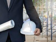 Инженер в костюме со светокопией и шлем в строительной площадке стоковое фото rf