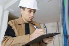Инженер в показателе примечания поступка в строительной площадке Стоковые Изображения RF