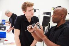 Инженер в фабрике с подмастерьем проверяет компонентное качество Стоковое Изображение RF
