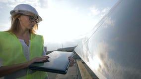 Инженер дамы солнечный заключителен ее компьтер-книжка и мельком взглядывающ в камеру видеоматериал