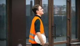 Инженер держа белую безопасность шлема на строительной площадке с краном стоковые фото