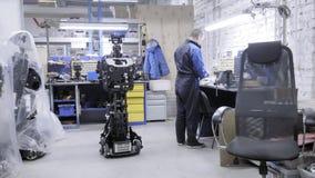 Инженер для его рабочего места Создает современный технический робот Демонтированный случай стоек робота рядом с сток-видео