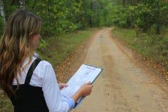 Инженер женщины на дороге леса с бумажным планом проекта конструкции стоковая фотография