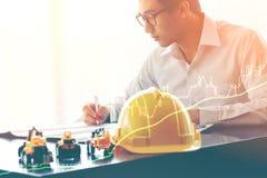 инженер или бизнесмен работая с промышленной двойной экспозицией чертежа проекта Стоковые Изображения RF