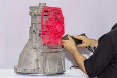 Инженер или оператор которого испускает розовый лазер света от портативного оборудования высокой точности развертки 3d к блоку пе стоковое фото