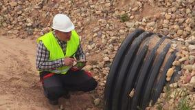 Инженер используя таблетку на дренажной траншее сток-видео