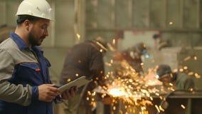Инженер используя ПК таблетки внутри в фабрике тяжелой индустрии Меля предпосылка искр сток-видео