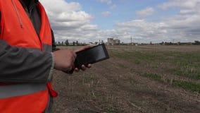 Инженер используя ПК таблетки на поле около фабрики акции видеоматериалы