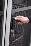 Инженер ИТ раскрывает дверь к шкафу сервера в datacenter Стоковое Изображение