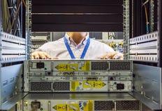 Инженер ИТ устанавливает JBOD для того чтобы положить на полку в datacenter стоковое фото rf