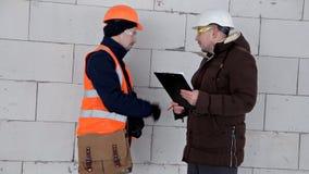 Инженер и архитектор обсудить план проекта Они имеют защитный шлем на их голове Работа, проект акции видеоматериалы