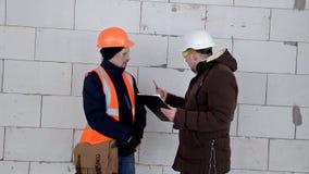 Инженер и архитектор обсудить план проекта Они имеют защитный шлем на их голове Работа, проект видеоматериал