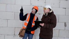 Инженер и архитектор обсудить план проекта Они имеют защитный шлем на их голове Работа, проект сток-видео