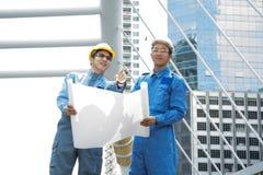 2 инженер или архитектор обсуждают на современном проекте строительства на Стоковое Изображение RF