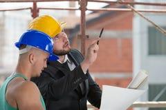 Инженер и рабочий-строитель обсуждая проект стоковые фото
